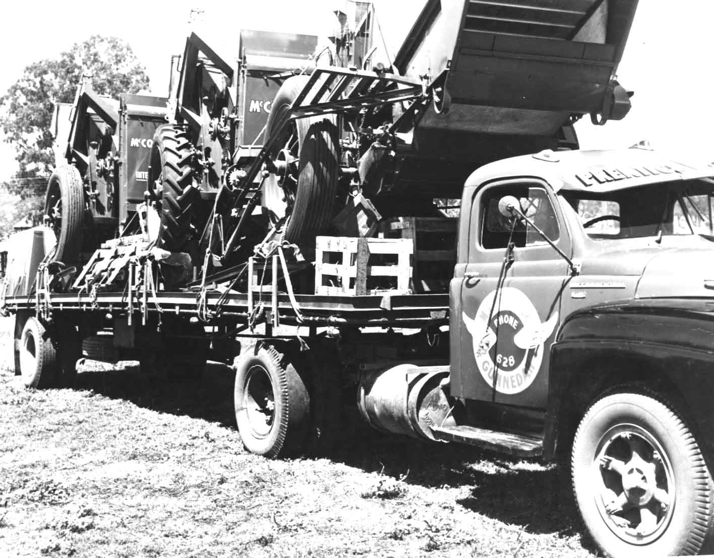 shows a AA series international truck with the single axle trailer loaded with three harvesters circa 1958